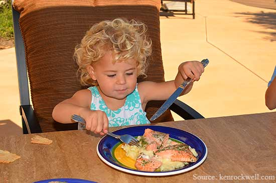 Kid eating salmon